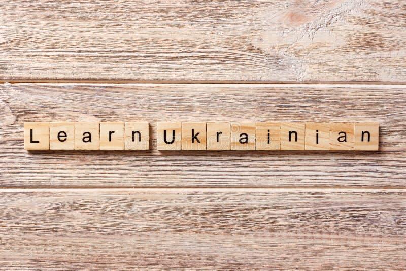Aprenda la palabra UCRANIANA escrita en el bloque de madera aprenda el texto UCRANIANO en la tabla, concepto foto de archivo libre de regalías