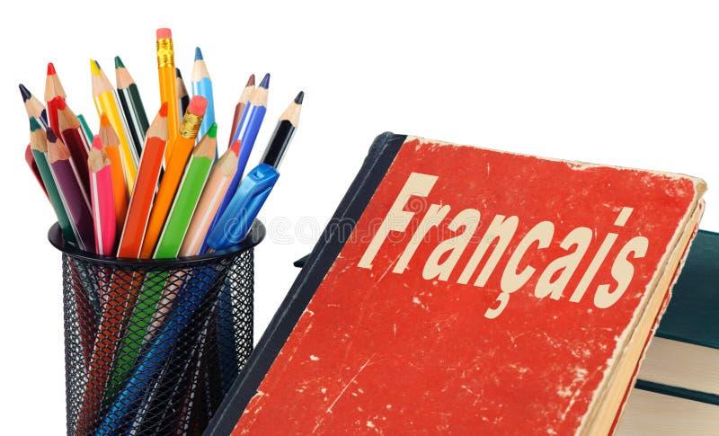 Aprenda o francês, o livro de texto e os lápis isolados fotografia de stock royalty free