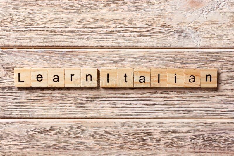 Aprenda a palavra italiana escrita no bloco de madeira aprenda o texto italiano na tabela, conceito foto de stock royalty free