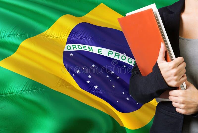 Aprendendo o conceito brasileiro da língua Posição da jovem mulher com a bandeira de Brasil no fundo Professor que guarda livros, fotografia de stock