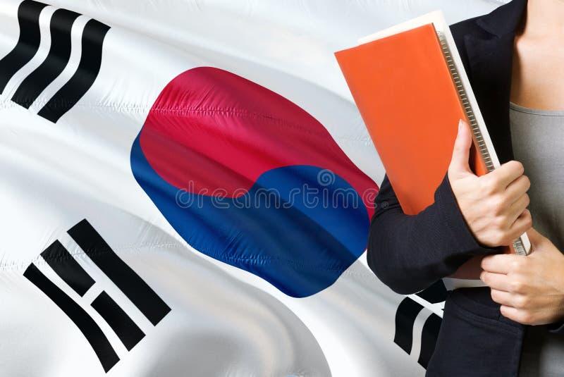 Aprendendo o conceito coreano sul da língua Posição da jovem mulher com a bandeira de Coreia do Sul no fundo Professor que guarda imagens de stock royalty free