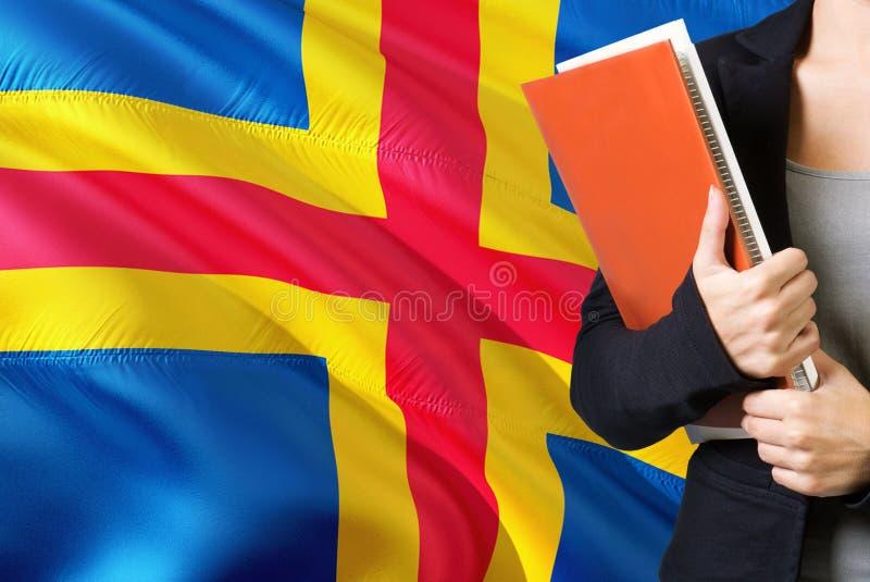 Aprendendo o conceito da l?ngua Posição da jovem mulher com a bandeira das ilhas de Aland no fundo Professor que guarda livros, p imagens de stock