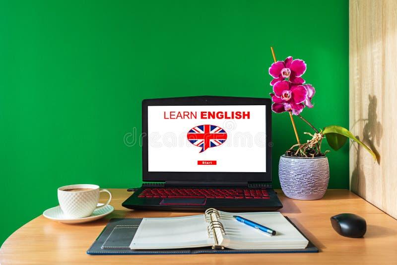 Aprendendo o conceito em linha inglês usando o computador Tela do portátil que indica o cartaz inglês das lições com bandeira bri fotos de stock