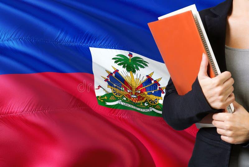 Aprendendo o conceito haitiano da língua Posição da jovem mulher com a bandeira de Haiti no fundo Professor que guarda livros, pl imagens de stock