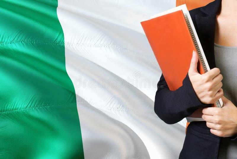 Aprendendo o conceito irlandês da língua Posição da jovem mulher com a bandeira da Irlanda no fundo Professor que guarda livros,  fotografia de stock royalty free