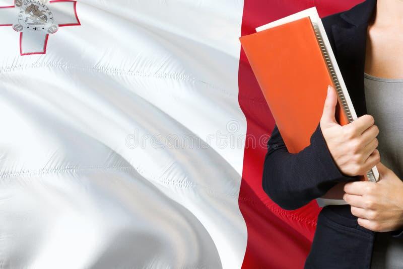 Aprendendo o conceito maltês da língua Posição da jovem mulher com a bandeira de Malta no fundo Professor que guarda livros, plac imagem de stock royalty free