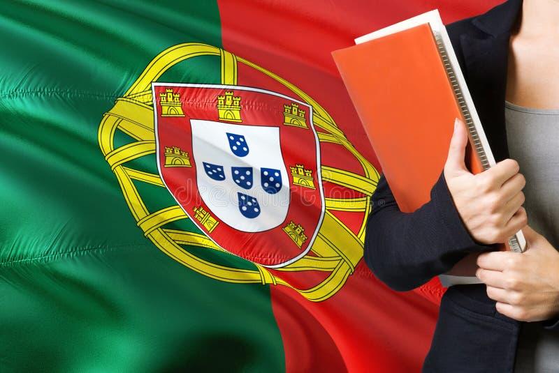 Aprendendo o conceito português da língua Posição da jovem mulher com a bandeira de Portugal no fundo Professor que guarda livros imagens de stock royalty free