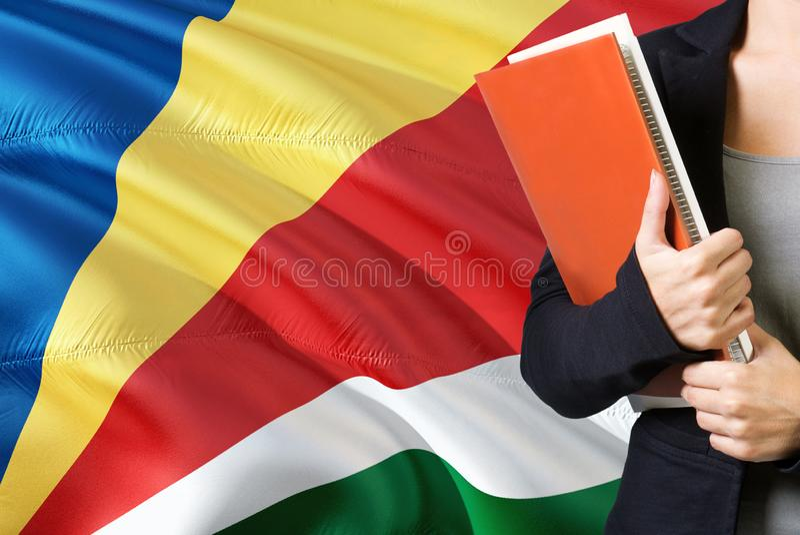 Aprendendo o conceito seichelense da língua Posição da jovem mulher com a bandeira de Seychelles no fundo Professor que guarda li fotos de stock royalty free