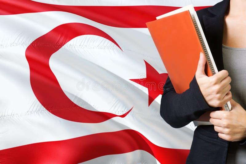 Aprendendo o conceito turco da língua Posição da jovem mulher com a bandeira do norte de Chipre no fundo Professor que guarda liv foto de stock