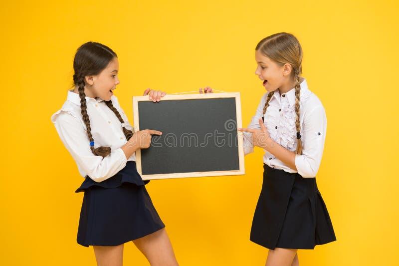 Aprendendo o divertimento na lição Alunos pequenos bonitos que relatam a lição no quadro-negro no fundo amarelo Estudantes pequen imagens de stock