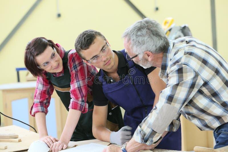 Aprendices jovenes que escuchan el instructor caprentry fotografía de archivo libre de regalías