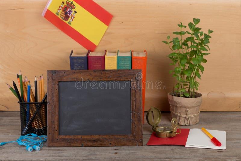 Aprendiendo el concepto de la lengua española - pizarra en blanco, bandera de la España, libros, lápices, compás imagen de archivo