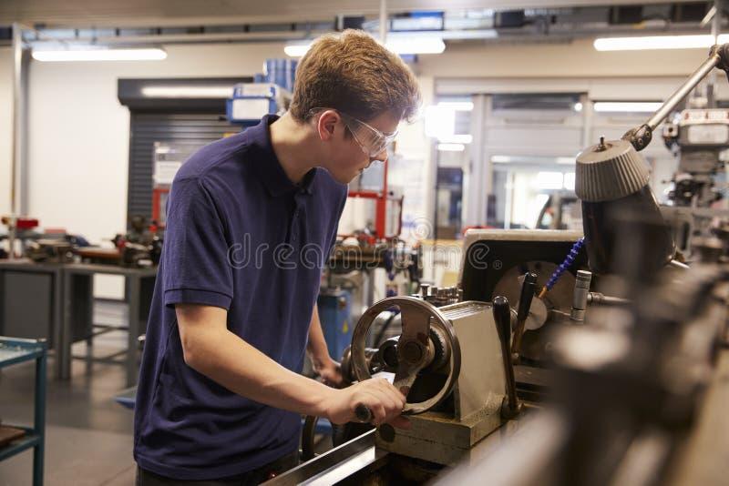 Aprendiz adolescente de sexo masculino en fábrica de ingeniería usando el torno imágenes de archivo libres de regalías