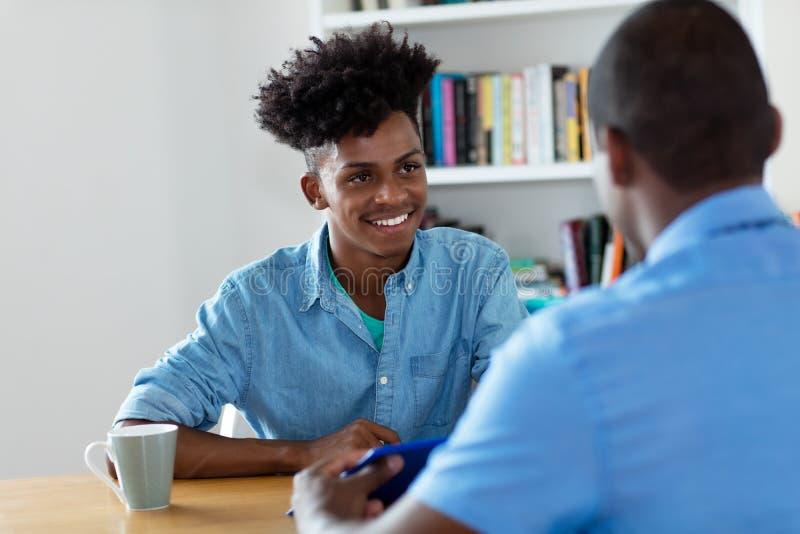 Aprendiz afroamericano y hombre de negocios negro en la entrevista de trabajo foto de archivo