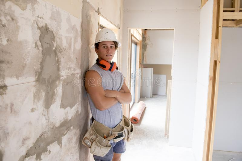 Aprendiz atractivo y confiado joven del trabajo del constructor y del constructor que aprende y que trabaja en el cuello azul del imagen de archivo libre de regalías