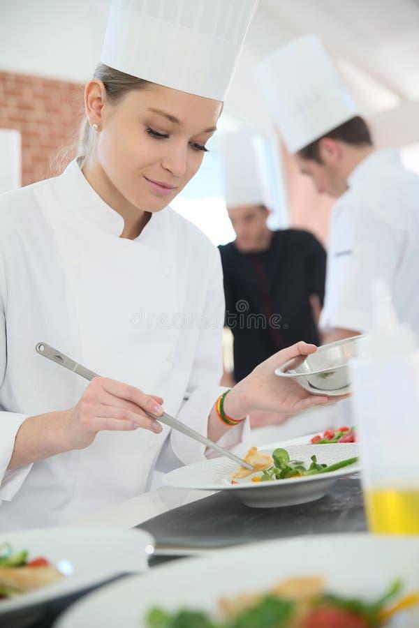 Aprendiz da jovem mulher que decora o prato imagens de stock royalty free