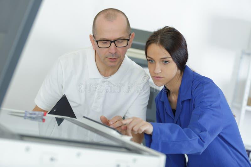 Aprendiz da jovem mulher que repara a fotocopiadora com mentor fotos de stock royalty free