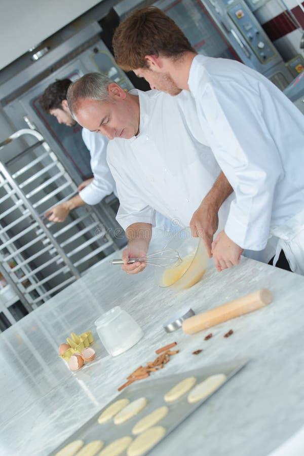Aprendiz de enseñanza del cocinero para hacer la corteza de los pasteles foto de archivo