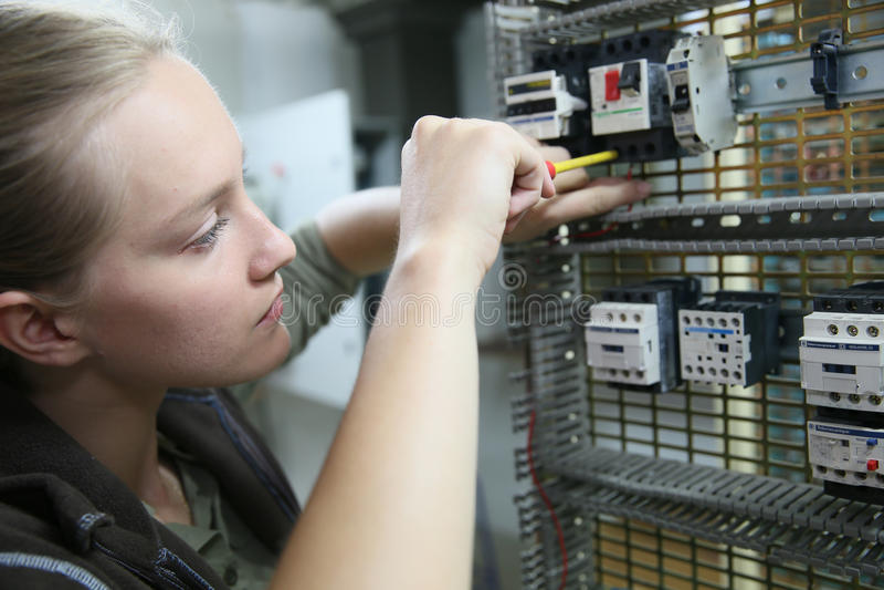 Aprendiz de la mujer joven en electrónica imagenes de archivo