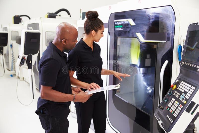 Aprendiz de sexo femenino que trabaja con maquinaria del CNC de On del ingeniero fotos de archivo libres de regalías