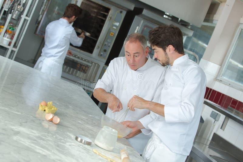 A aprendiz del chef mostrando cómo preparar la pasta fotos de archivo