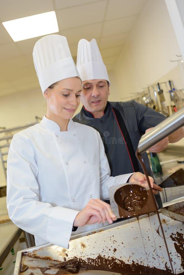 Aprendiz del trabajador de sexo femenino que hace el chocolate imagenes de archivo