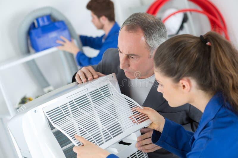 Aprendiz fêmea que aprende reparar o compressor industrial do condicionamento de ar fotografia de stock royalty free