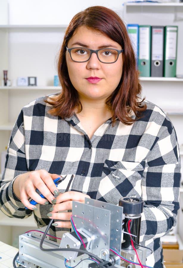 Aprendiz fêmea que trabalha na maquinaria do CNC fotografia de stock royalty free
