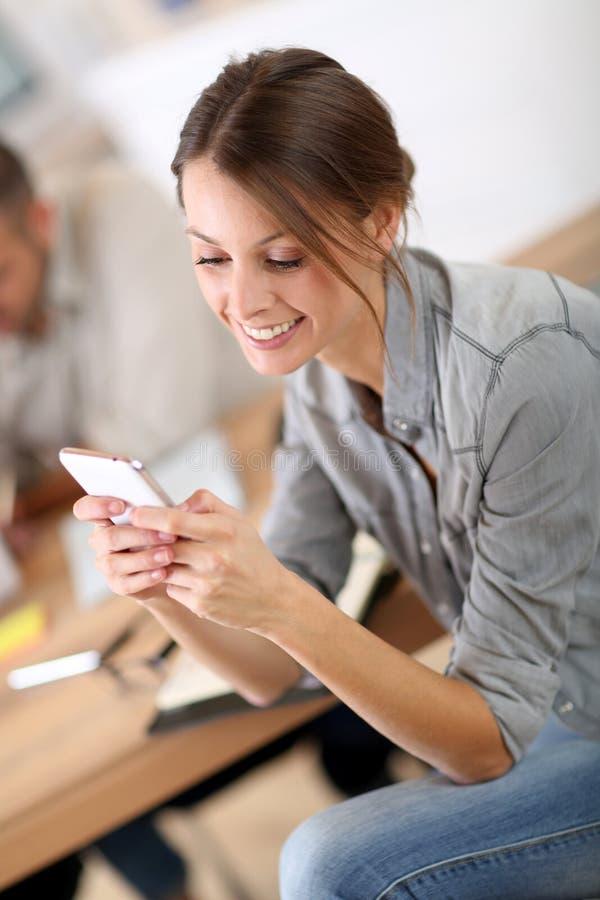 Aprendiz joven en clase de negocios usando smartphone imagenes de archivo