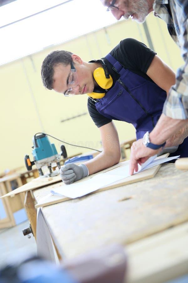 Aprendiz joven en curso de la carpintería imagenes de archivo