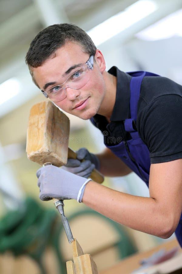 Aprendiz joven en taller de la carpintería imagenes de archivo
