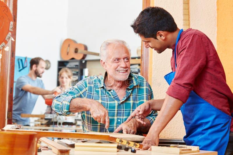 Aprendiz más luthier principal de las ayudas imagen de archivo libre de regalías