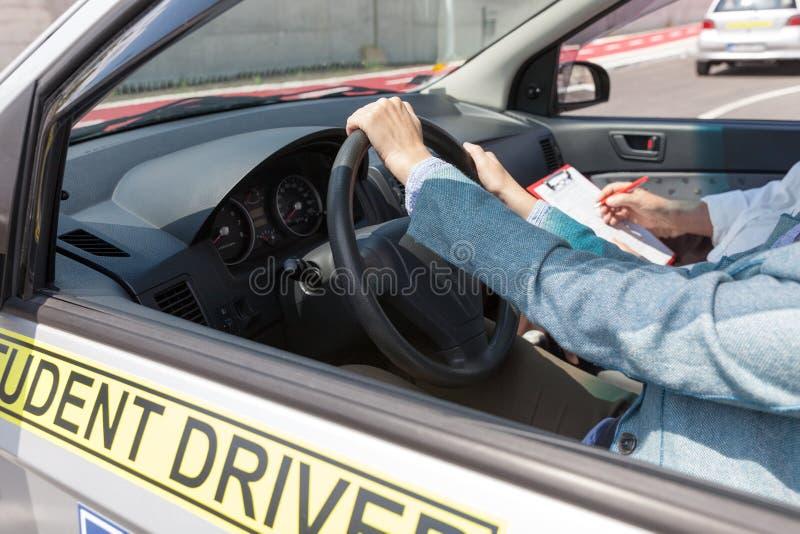 Aprendizagem conduzir um carro com um instrutor de condução Movimentação do estudante fotografia de stock royalty free