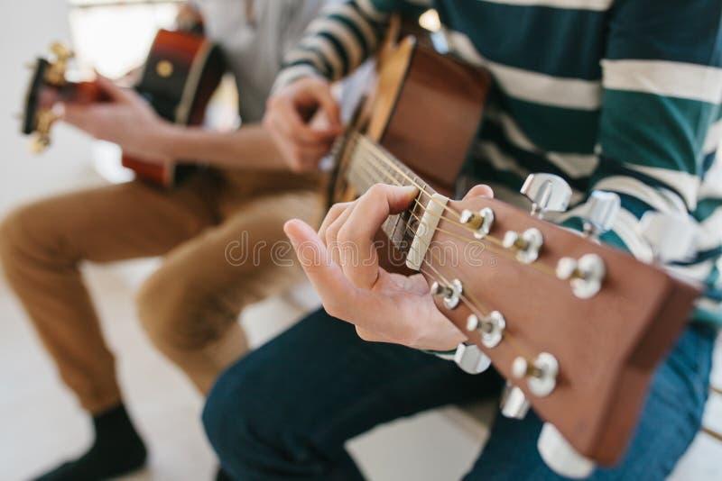 Aprendizagem jogar a guitarra Lições da educação e do extracurricular da música Passatempos e entusiasmo para jogar a guitarra e fotos de stock royalty free
