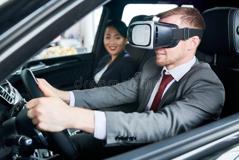 Aprendizaje conducir el coche con las auriculares de VR fotografía de archivo