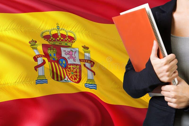Aprendizaje de concepto de la lengua española Situación de la mujer joven con la bandera de España en el fondo Profesor que sosti fotografía de archivo