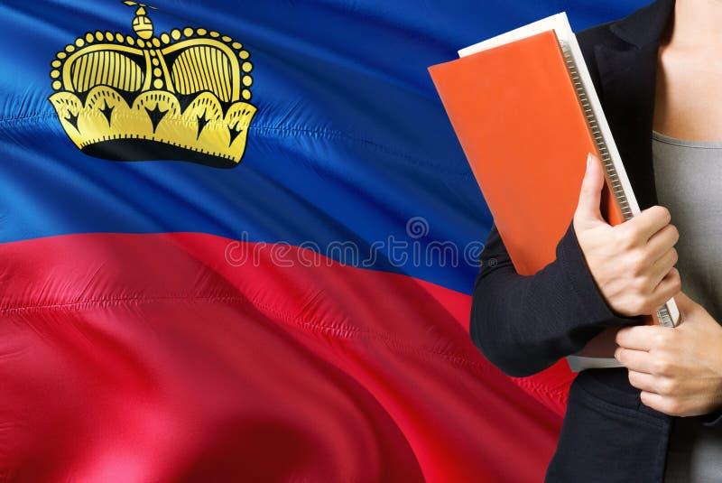 Aprendizaje de concepto de la lengua de Liechtensteiner Situación de la mujer joven con la bandera de Liechtenstein en el fondo T imagen de archivo