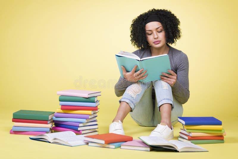 Aprendizaje enfocado de la muchacha del estudiante rodeado por los libros coloridos imagen de archivo