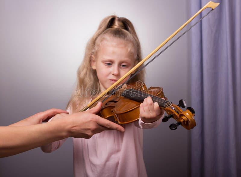 Aprendizaje jugar La niña intenta sostener correctamente la herramienta fotografía de archivo