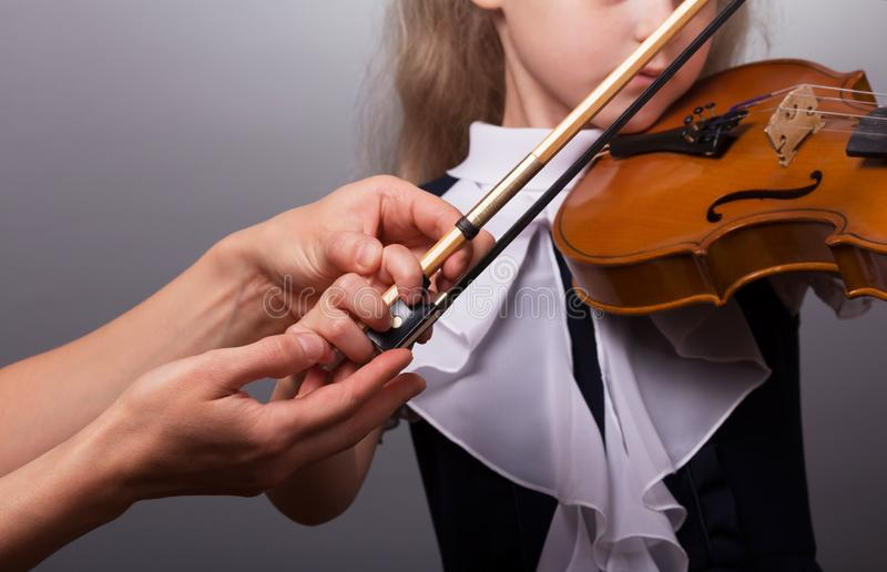 Aprendizaje jugar La niña y el profesor toca el violín imagen de archivo