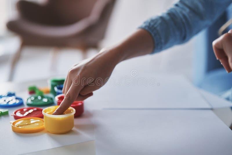 Aprendizaje pintar Ciérrese para arriba de las pinturas conmovedoras de la niña mientras que fotografía de archivo libre de regalías