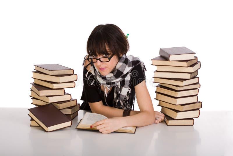 Aprendizaje y lectura entre la pila dos de libros imagen de archivo