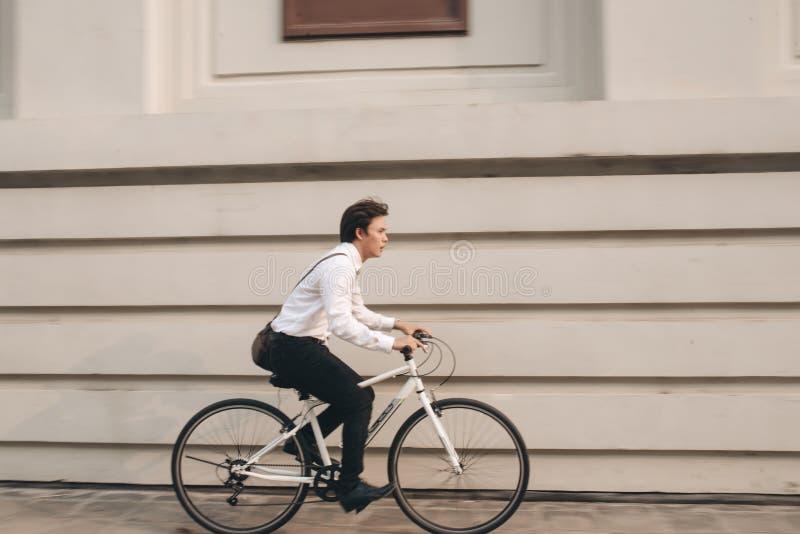Apresúrese la bici asiática del montar a caballo del hombre de negocios sobre hora punta Lat del hombre joven fotografía de archivo