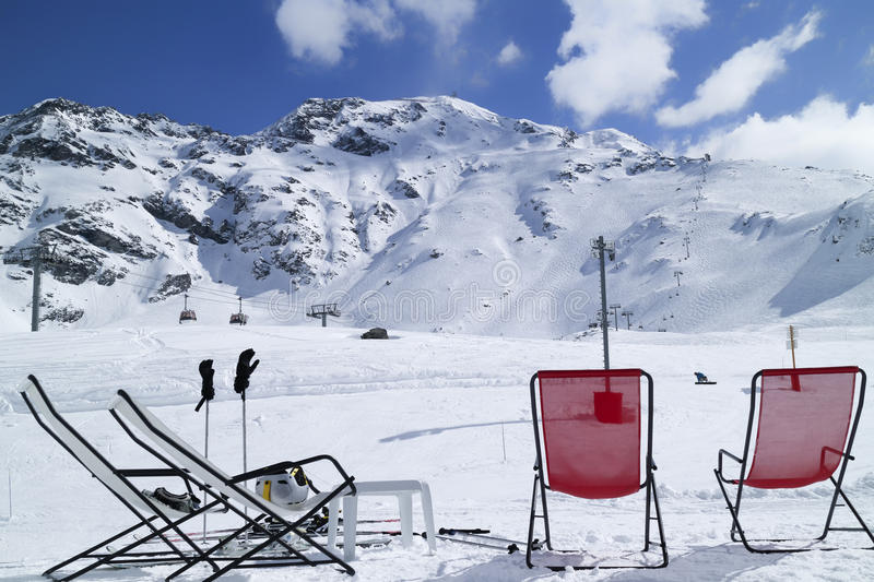 Apres ski on snow in French Alps. Red and white relaxing lounge chairs on snow in front of ski piste and lifts, in alpine winter resort of Les Arcs, France stock images