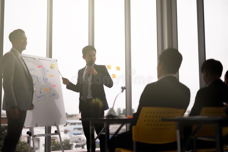 Apresentação de dois homens de negócios em uma sala de reunião da conferência e em uma audiência do conferente foto de stock royalty free