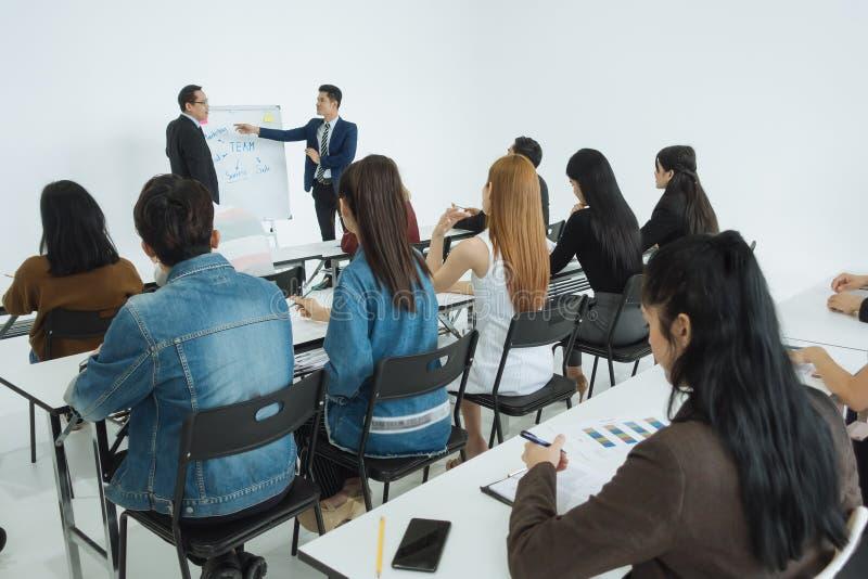 Apresentação de dois homens de negócios em uma sala de reunião da conferência e em uma audiência do conferente imagens de stock