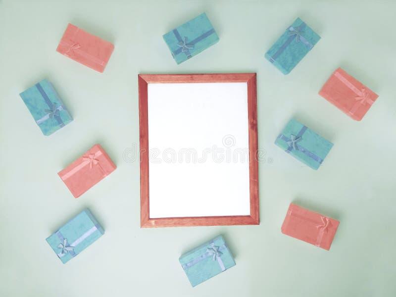 Apresentação vazia da almofadinha do quadro e muitas caixas de presente no fundo verde imagens de stock