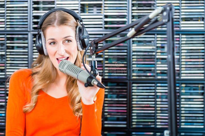 Apresentador de rádio fêmea na estação de rádio no ar imagem de stock