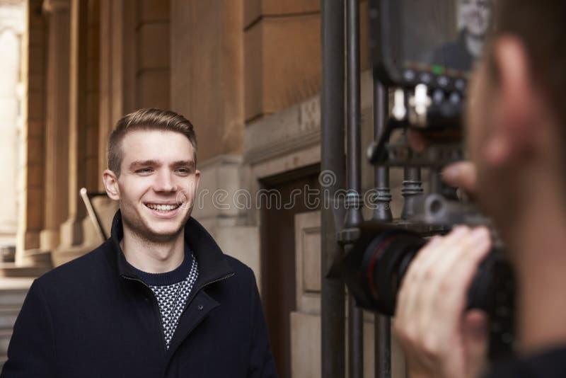 Apresentador masculino Filming Outdoor Report da televisão foto de stock royalty free