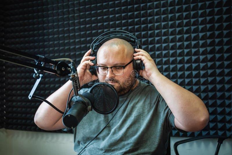 Apresentador ou anfitrião de rádio gordo no estúdio da estação de rádio com fones de ouvido e microfone, retrato do homem de func imagens de stock royalty free